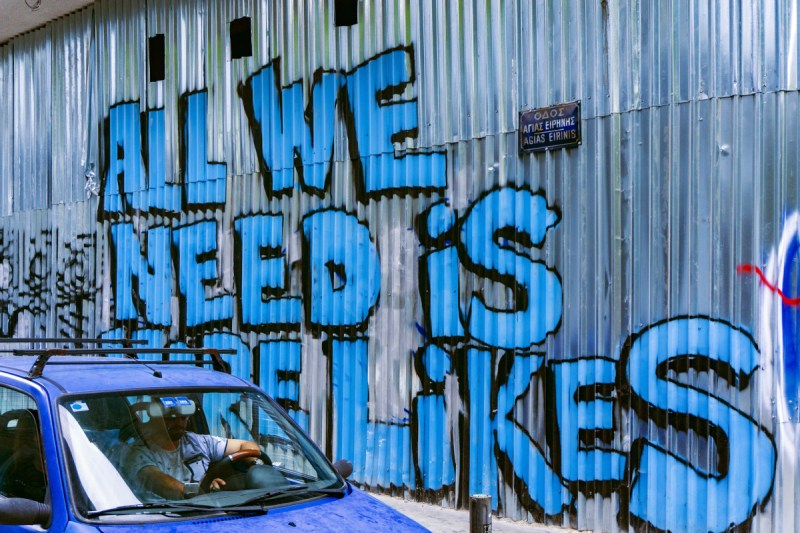 """Graffiti saying """"All we need is more likes"""""""
