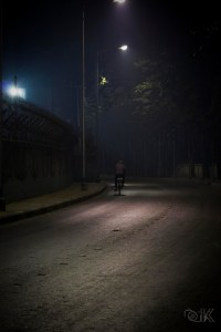 Man riding a cycle on an empty road lit with streetlights.