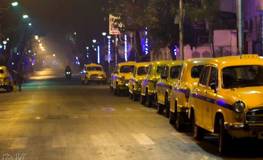 Peeli taxi 's parked in an order on the side of an empty road