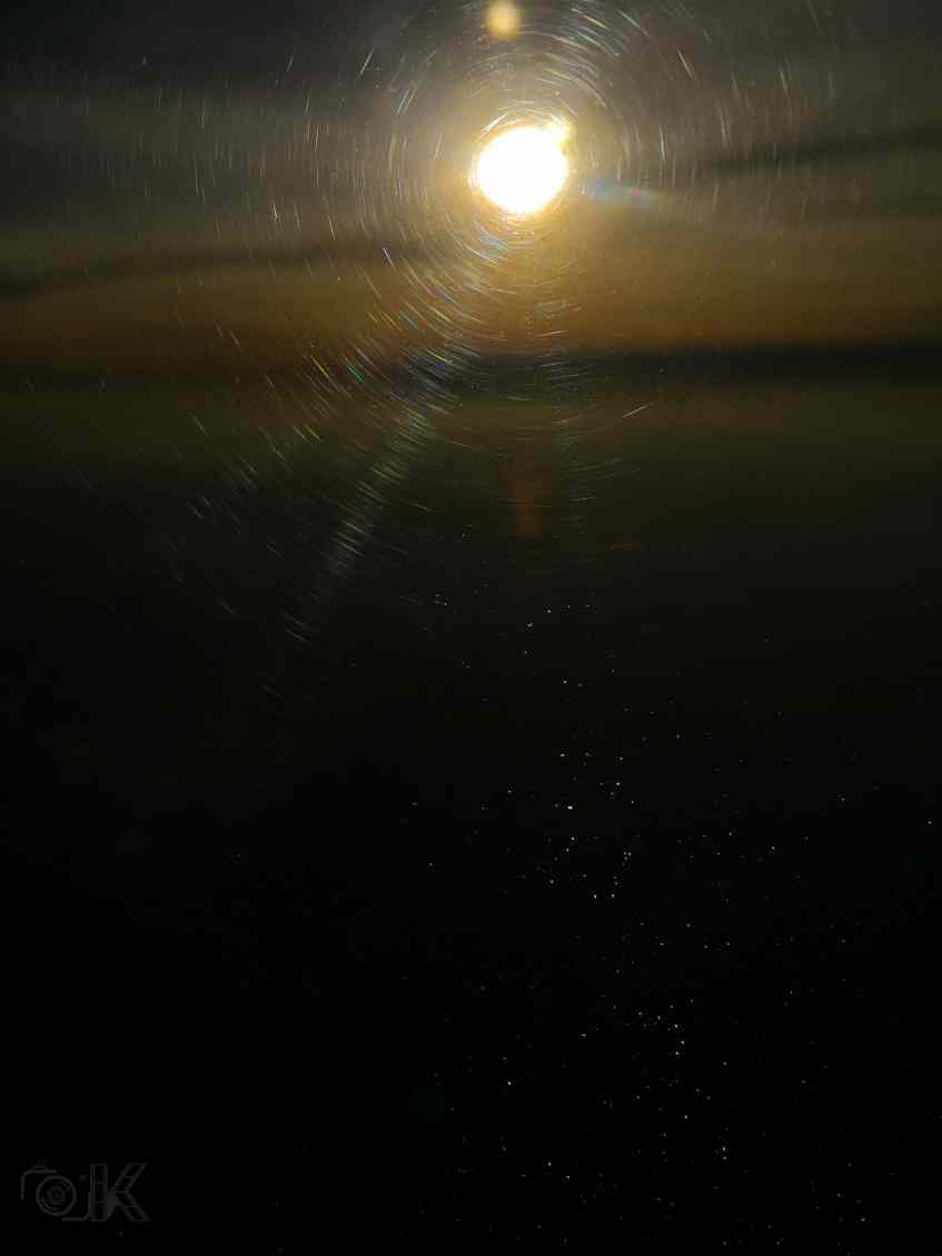 The pale orange light from sunset creating a disk pattern on the worn out screen of window