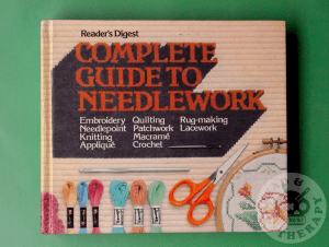 Reader's Digest Complete Guide to Needlework book against a green backdrop.