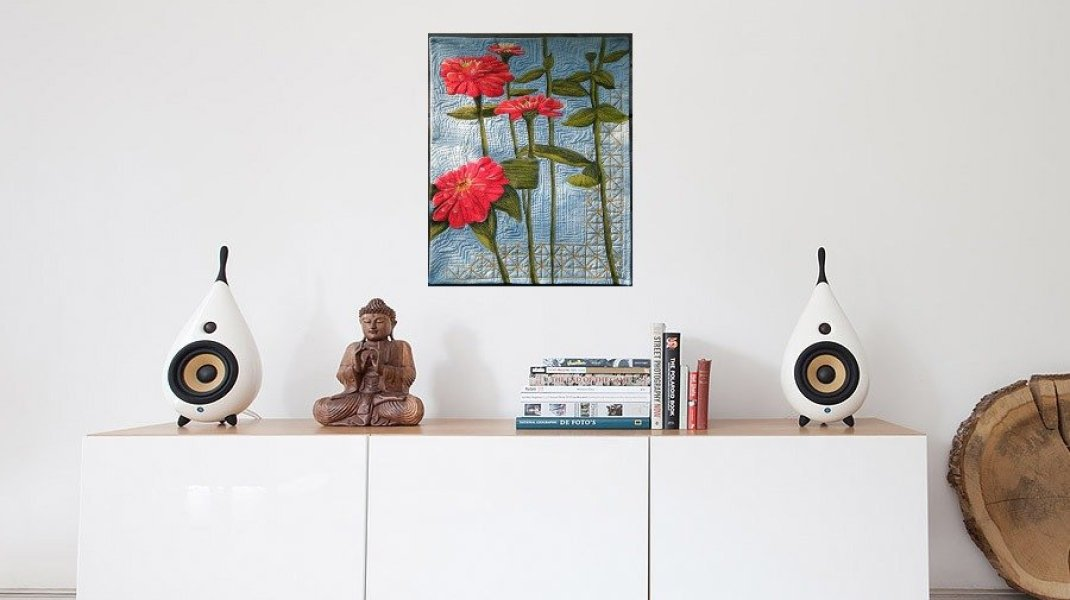 Thread painting of zinnias set with a living room sideboard , Buddha and candles