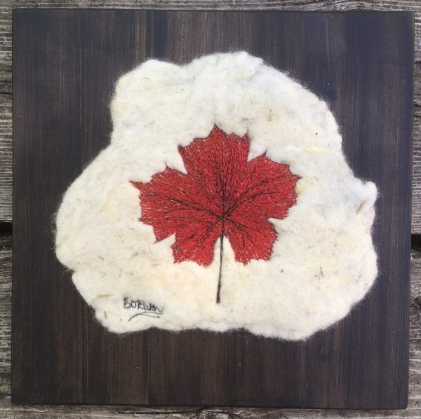 Thread painted red maple leaf on felt