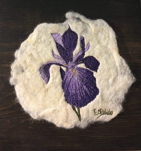 Embroidered iris on felt mounted on pine