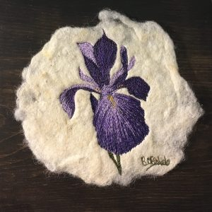 Embroidered iris on felt mounted on pine