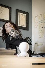 woman hugging cat in office