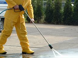 Man in yellow waterproofs pressure washing slabs