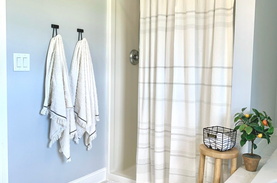 modern farmhouse style shower with hearth and hand cream towels and shower curtain, plush chunky knit bathmat, and a cute stool with basket and clementine tree