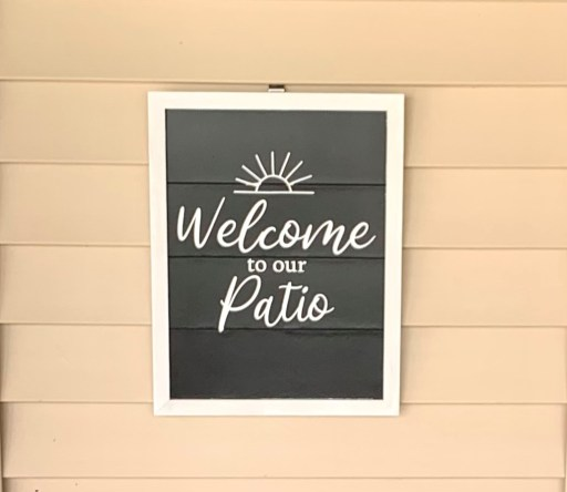 black and white framed 'welcome to our patio' diy outdoor wood sign