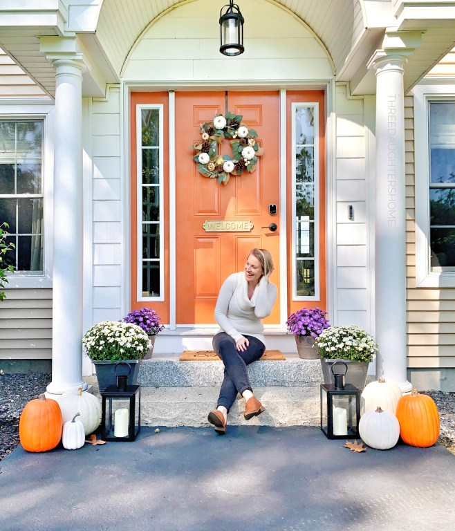 festive fall entry steps with an orange door and cascading flowers and pumpkins
