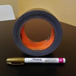 A roll of black duct tape and a gold ink Sharpie marker.