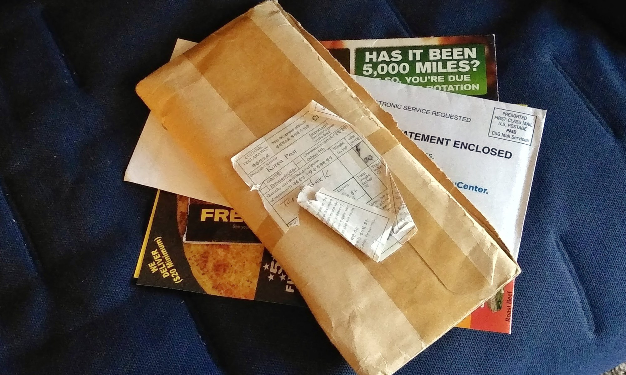 "A pile of mail with a small, thin, brown wrapped package on top. The package has a customs declaration sticker on it that shows it was sent via Korea Post. However, the sticker is ripped and folded onto itself, so that the handwritten words ""Tarot Deck"" is partially obscured and the receipient's address is completely hidden. The side of the package has been cut open to preserve the wrapping as a protective covering of the contents."