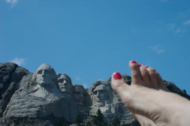 Lou Nell's bare right foot w/pink toenails, Mt. Rushmore and blue sky in background