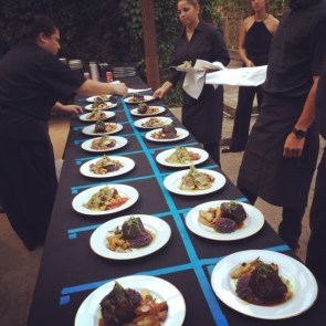 The Three's team plates food at an event.