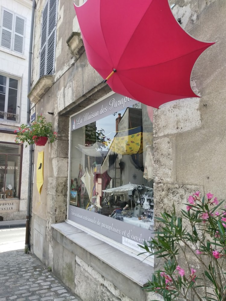 A bright red umbrella in front of a shop window with pretty potted plants
