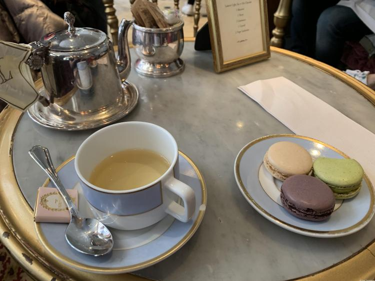 Tea at Ladurée with a blue and white china cup and 3 macarons of various colors and a silver teapot