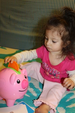 brunette girl child putting orange coin in pink piggy bank