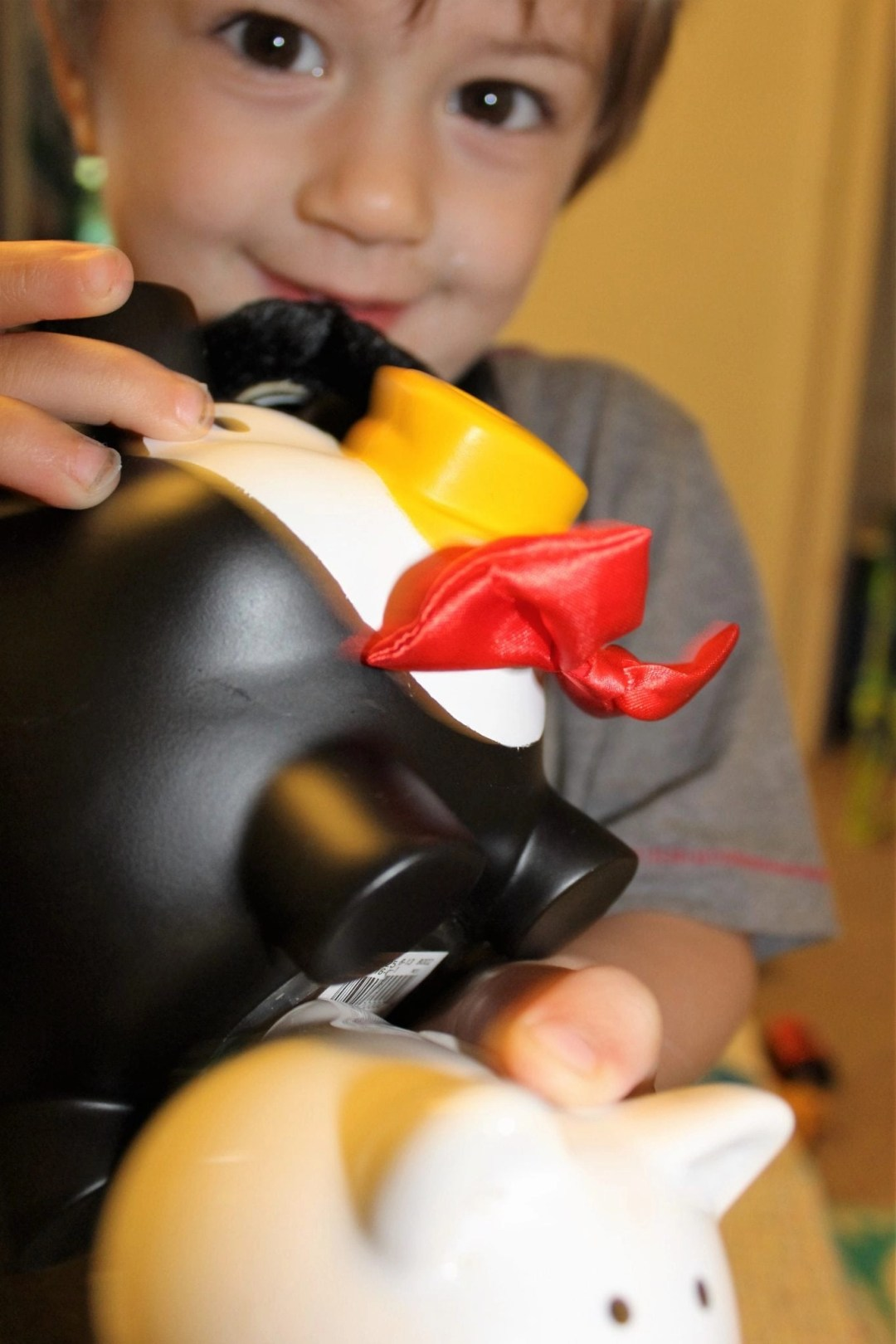 blonde toddler holding black and white piggy bank