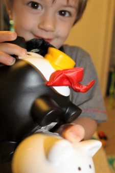 blonde male child holding a black and white piggy bank