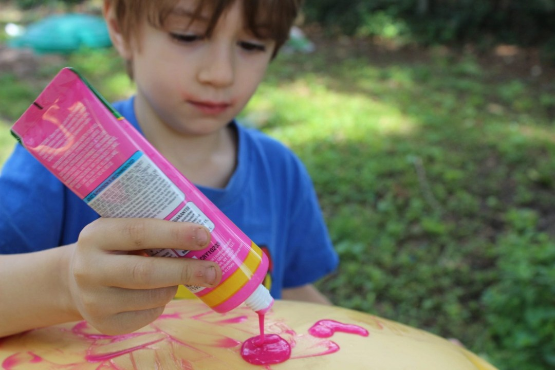 blonde toddler squeezing pink paint out of tube
