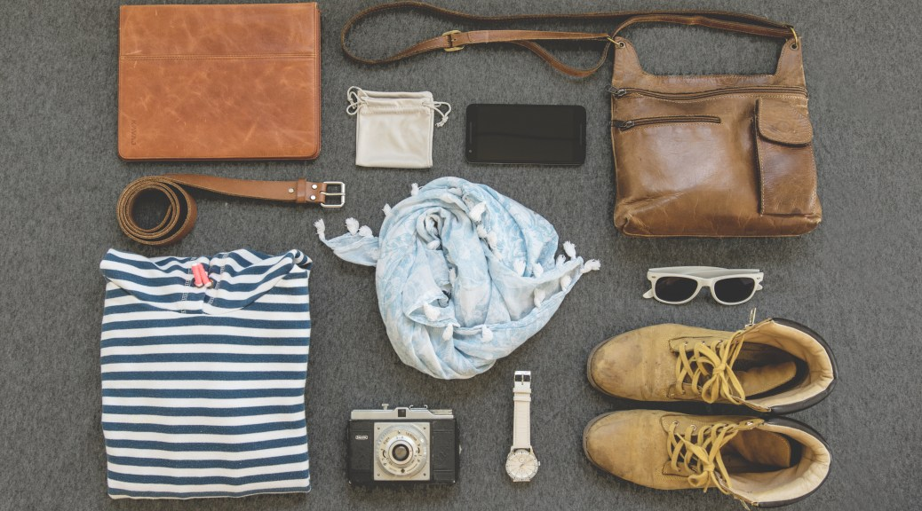 Flatlay of various items, sunglasses, leather bag, watch, shoes, belt