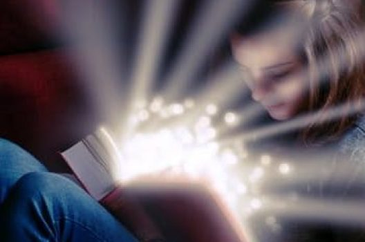 girl reading book with light shining
