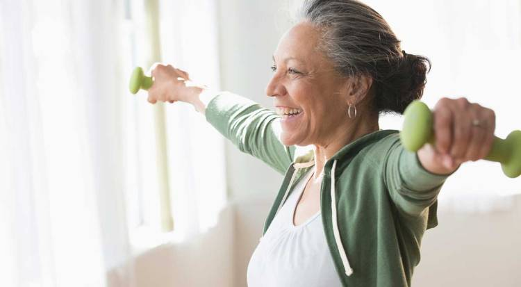 An older woman smiles while lifting two small green weights in her hands.