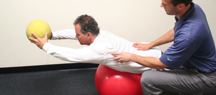 Dr. Kauffman treating a patient with movement and weight training using balls.