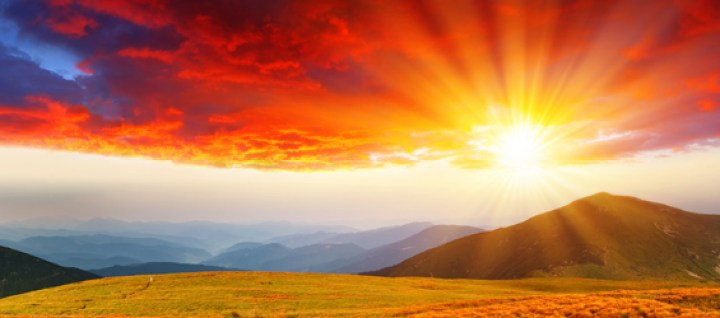 A beautiful sunset with mountains and hills and vibrant orange and red colors.