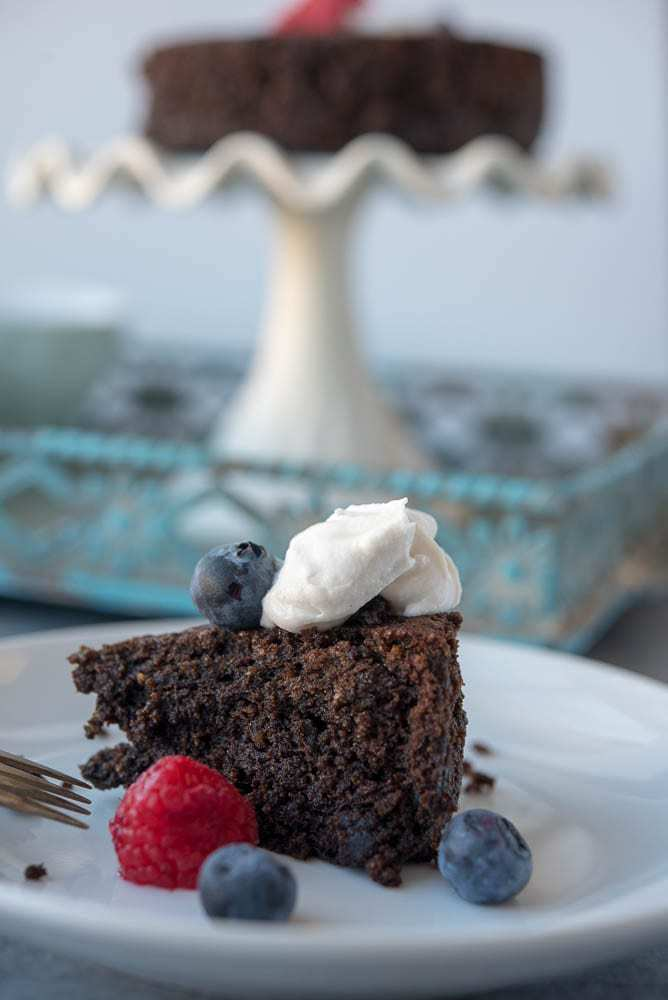 A scene with a closeup of a slice chocolate cake and the rest of the cake in the background