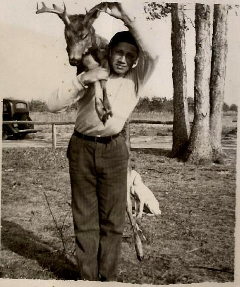 A vintage hunting photograph of a Teen-Aged Boy Carrying a Buck White-tailed Deer Over His Shoulder Which He Harvested With a Shotgun in the Late 1930's in Southern New Jersey. The deer hunter is Mark A. McCarty Sr.