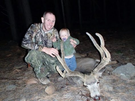 An arizona bowhunter poses with a mule deer trophy, along with a future bowhunter