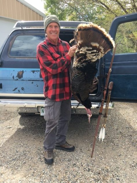 a colorado bowhunter poses with a wild turkey harvested with a recurve bow in spring of 2017