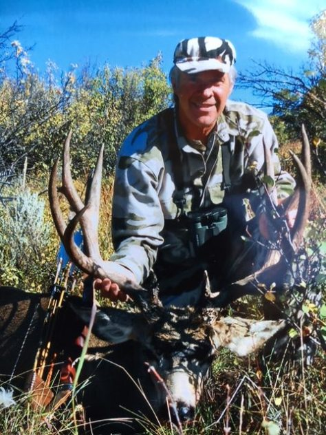 A traditional archer poses with a pope and young class mule deer buck taken in northwestern colorado.