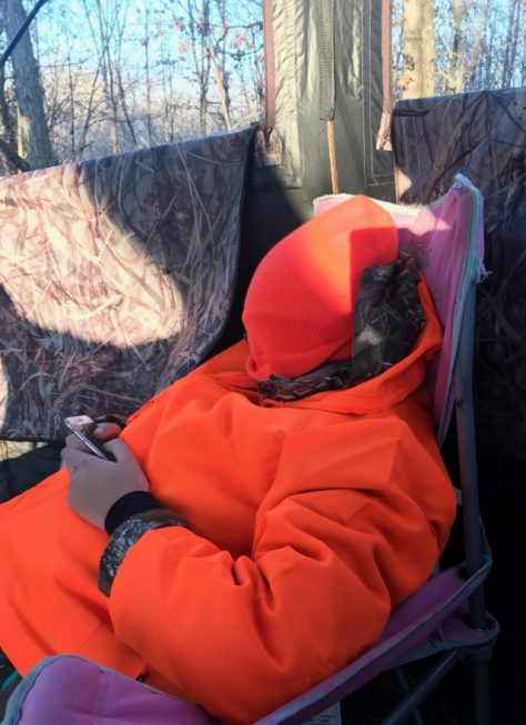 A Young Wisconsin White-tailed Deer Hunter Reacts After Missing a Buck...By Pulling Her Hat Over Her Head and Texting On Her Smart Phone