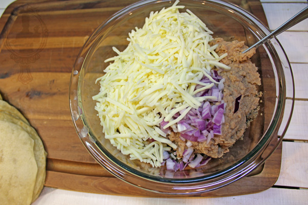 Bowl with refried beans, browned ground beef, cheese and onions.