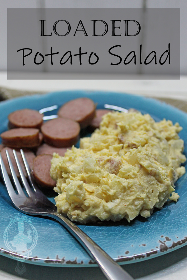 A plate with a serving of Loaded Potato Salad and sliced up turkey sausage and a fork laying on the plate ready to scoop up a bite.