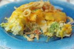 Serving of Chicken Broccoli and Rice Casserole on a blue plate with a bite on a fork ready to eat.