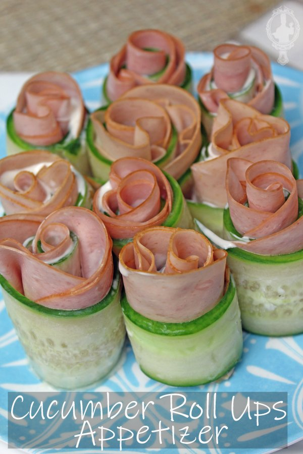 Angle view of the cucumber roll ups on a blue plate.