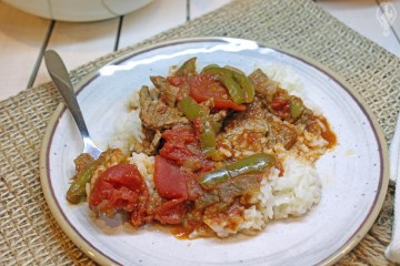 A plate with pepper steak on top of a bed of rice.