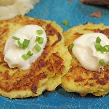 Two squash fritters with sour cream and green onions on top.