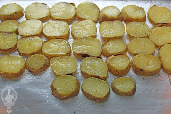 Sliced potatoes on a baking sheet with oil.