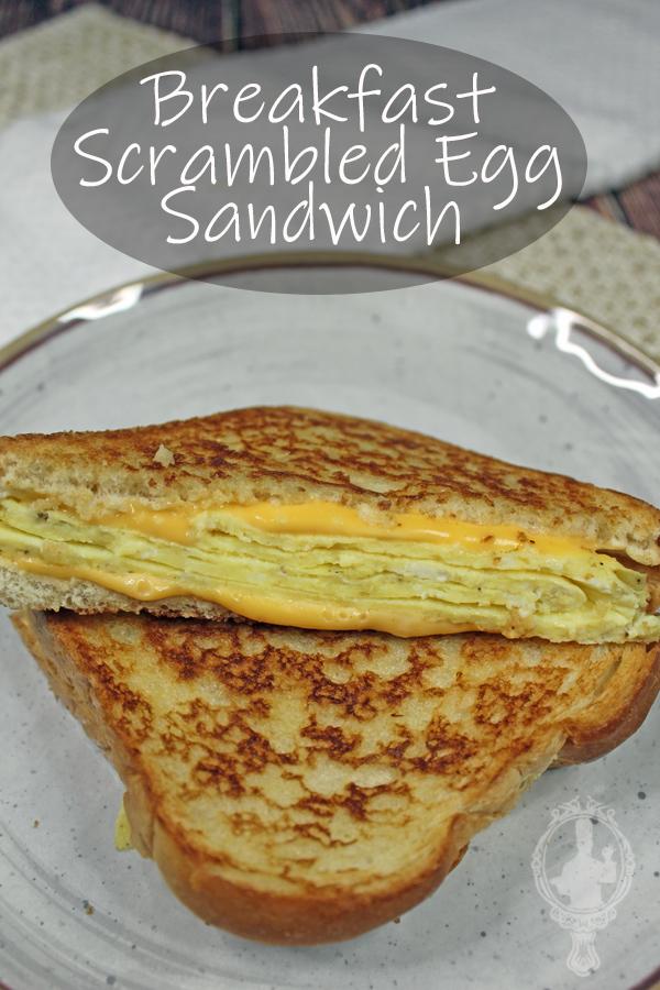 A scrambled egg sandwich cut in half on a plate.