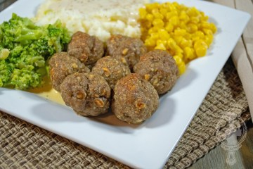 A plate with meatballs, broccoli, mashed potaoes & gravy, and corn.