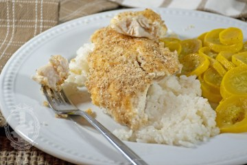 A serving of parmesan crusted tilapia with a bite removed.