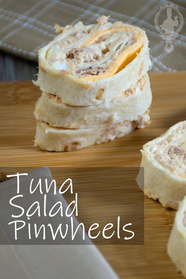 A stack of tuna salad pinwheels on a cutting board.