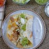 Overhead view of an open bean burrito with lettuce, guacamole and sour cream added.