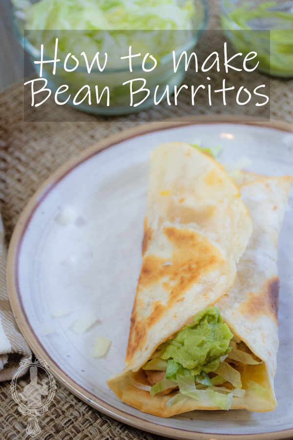 A closed bean burrito on a plate with condiments/lettuce in the back.