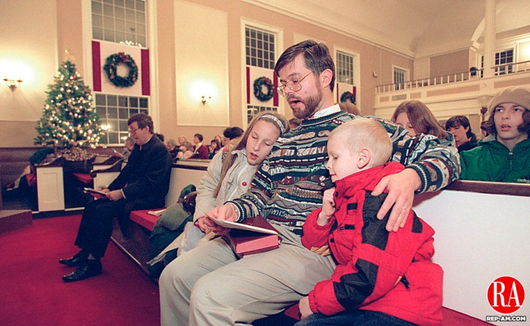 THOMASTON, CT 12/13/98 --1213JH07.tif--Rev. Peter Smith of the First Congregational Church of Thomaston sits in a front row pew with his kids Coralie, 9, left, and Ben, 6, right, as the annual Christmas Walk brought people into his church Sunday night. JOHN HARVEY staff photo for Bednar story.