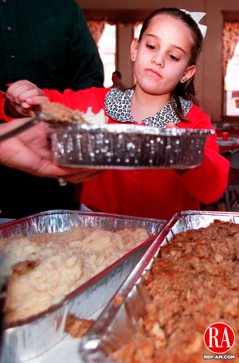 NAUGATUCK, CT 12/25/98--1225DC04.tif      Seven year old Laura Berey serves a helping of mashed potatoes during the Ecumenical Conference of Churches Christmas Day DInner at St. Michael